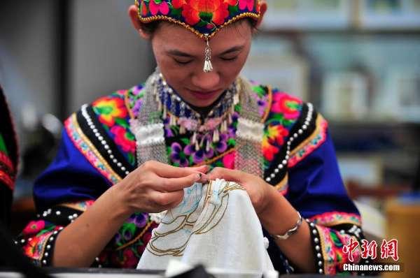 彝族刺绣非遗传承人正在做作业