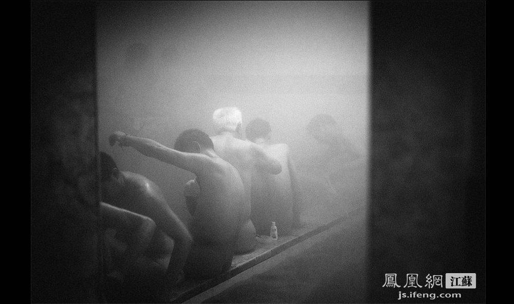 """周师傅(中间白发者)在帮他儿子擦背。周师傅今年88岁,一个星期来这泡两三次澡,大都由儿子陪同。老人称,年轻时就爱泡澡,现在年纪大了,更爱泡澡了。""""(智德商旅--黄埔7号影像俱乐部/图 胥大伟/文)"""