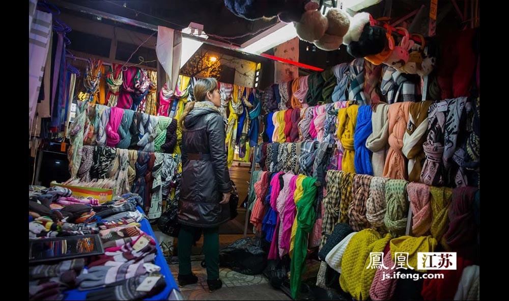 """丹凤街夜市的小摊贩主要卖衣服、鞋子、被子、锅碗瓢盆等日用品。来这里逛夜市的主要是周边居民以及附近高校的""""穷学生""""。管理方晚上11点准时拉闸关电,夜市到此结束。(林琨/摄 胥大伟/文)"""