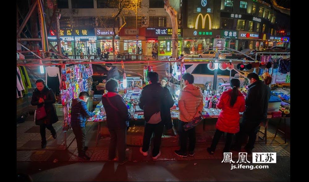 在丹凤街夜市,玩具和日用小百货比较受欢迎。夜市摊贩一街之隔,就是装修现代的一排店面。(林琨/摄 胥大伟/文)