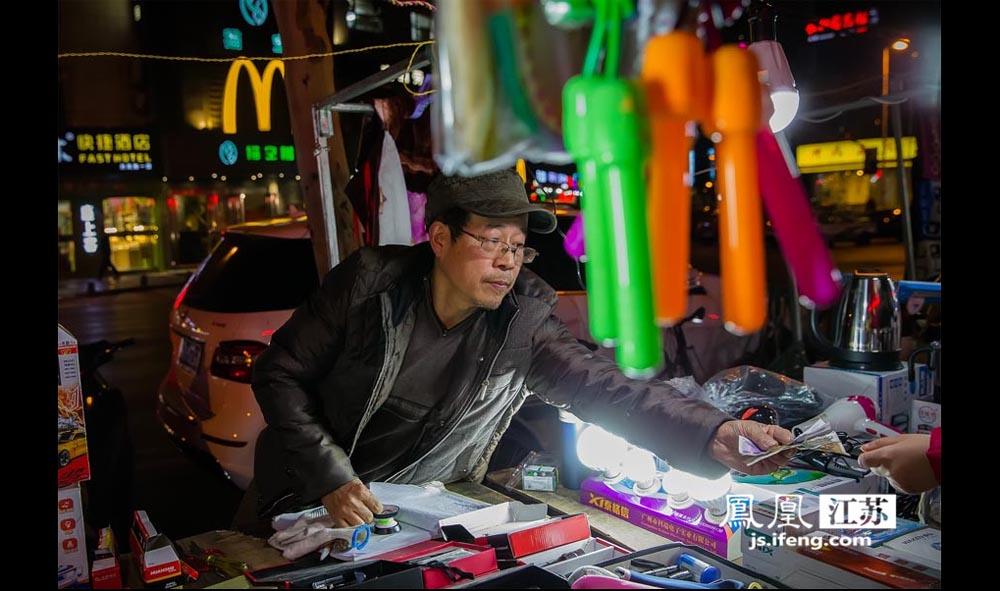 """李培根是个有着20多年的摆摊史的""""老江湖"""",2006年来到丹凤街,主要卖些玩具和小百货。""""都是些小玩意,勉强糊口。""""他原来在工厂上班,每月工资只有几百元,后来李培根下岗了。""""我都是56岁的人了,打工谁会要?""""(林琨/摄 胥大伟/文)"""