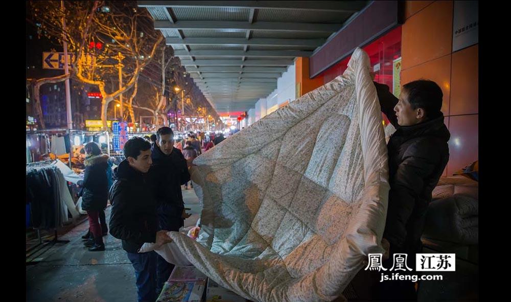 """两位外国留学生在陈正来(右)的摊位上挑选被子。陈正来是安徽人,当了20几年的小摊贩,自称是南京夜市""""第一批吃螃蟹的人。""""陈正来先后""""转战""""新街口、洪武路、珠江路等南京夜市。陈正来回忆,2000年前后是南京夜市最火的时候,""""东西越贵越有人买,在浙江进的衣服进价几十元转手就卖一百多。""""(林琨/摄 胥大伟/文)"""