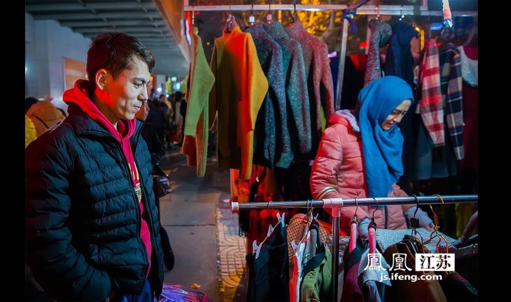 """阿卜杜艾尼(左)和女朋友在夜市选购衣服。当摊贩老板夸他的女朋友漂亮时,他揶揄道:""""漂亮你就给我们便宜点。""""阿卜杜艾尼是新疆喀什人,目前就读于河海大学水文专业,今年毕业。阿卜杜艾尼在南京读了4年大学,时常会和朋友来逛夜市。他说希望这样的夜市能在南京多一点,""""因为这里的东西物美价廉。""""(林琨/摄 胥大伟/文)"""