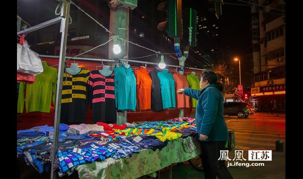 一位妇女在一处摊位前挑选衣服。(林琨/摄 胥大伟/文)