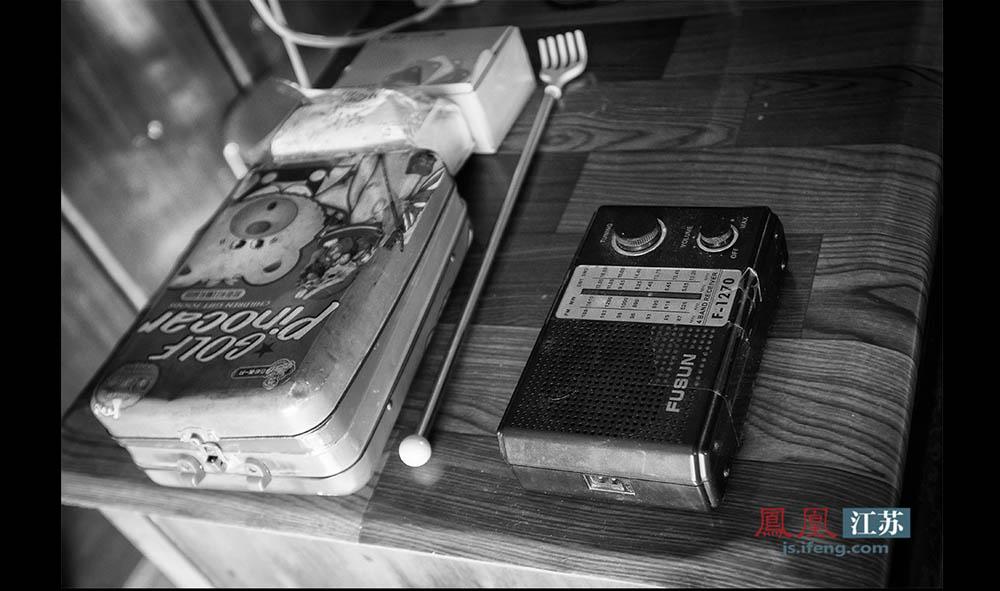 船上的生活单调乏味,常常收不到电视信号,加上船上无法通电,王扣子那台破旧的电视机就成了摆设,夫妻俩只能靠听收音机打发无聊的时间。(林琨/摄 胥大伟/文)