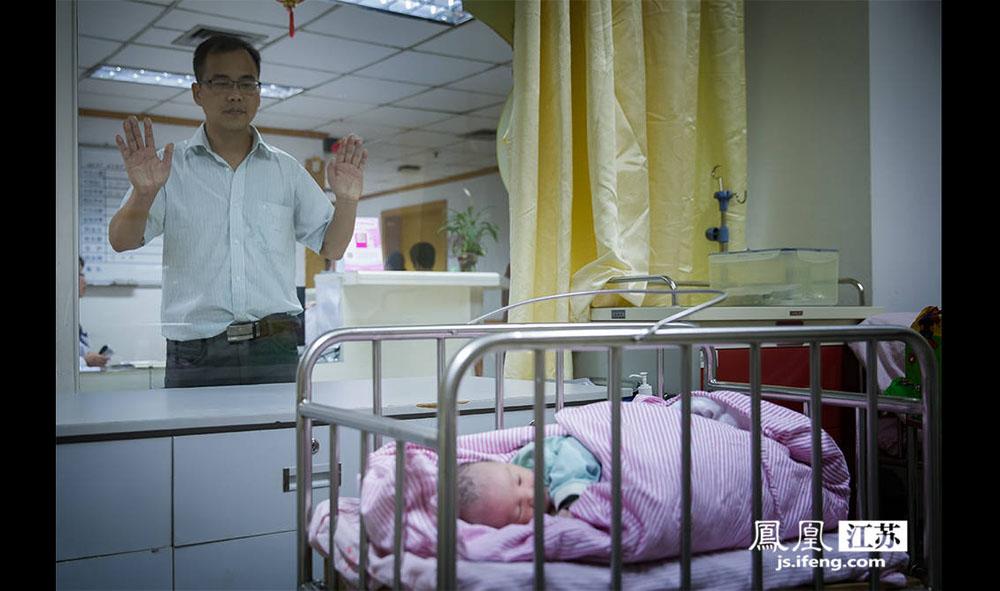 """箫涛透过产房外的玻璃探望自己刚出生的儿子。6月16日上午9点,妻子剖腹生下了他们第一个孩子。今年30岁的箫涛来自广西,第一次当爸爸,说很紧张。箫涛说自己第一个父亲节的愿望就是""""母子平安,好好把孩子养育成人。""""(林琨/摄 胥大伟/文)"""