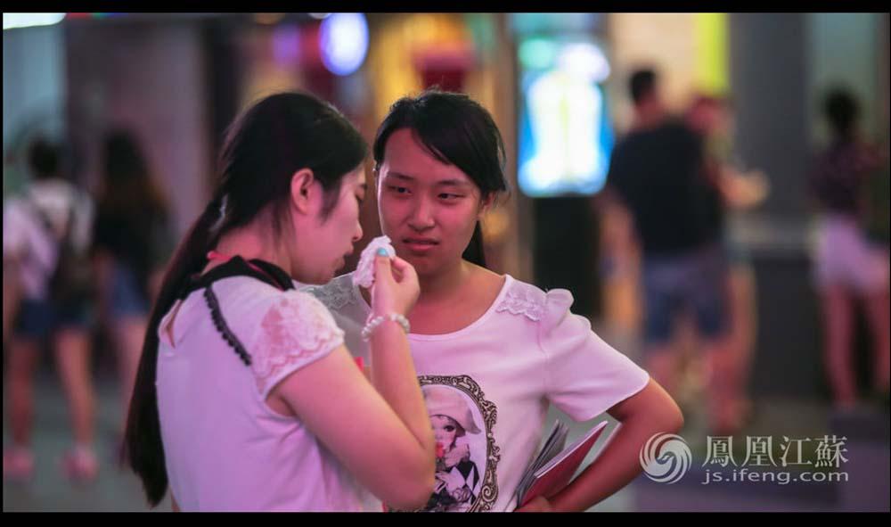 天色渐暗,大街上霓虹亮起,张孝娟的同事(左)因为今天没能带到有意向的学员,遇到的路人态度也都比较冷漠,站在大街上委屈地哭了,张孝娟在一旁试图安慰她。(魏玮/文 汤霖、杨光泽/图)