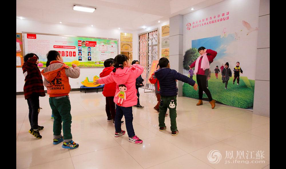 """南京的冬天潮湿阴冷,老师每天会带领小朋友们在大厅里跳舞热身。当《小苹果》欢快的音乐响起时,孩子们显得异常兴奋。老师说,由于许多孩子属于重度听力障碍,即使戴着助听器,他们也只能""""断断续续地听见一点点声响"""",""""有些孩子还患有脑瘫等疾病,肢体协调性很差,跳得不那么优美,但他们都很快乐""""。(胥大伟 徐然/文 毛寿皓/图)"""