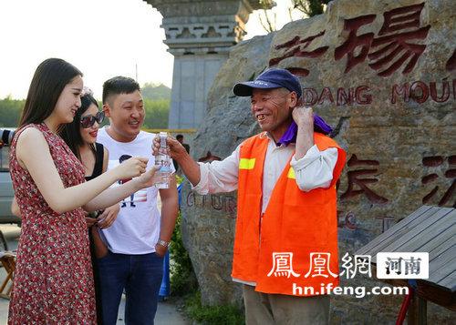 游客在芒砀山景区为环卫工人送水图片走红网络