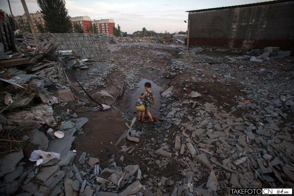 暴雨过后,村庄被冲垮,一对双胞胎在瓦井村废墟的水池边玩耍。