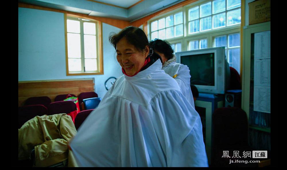 午后,一名老年唱诗班的女信徒穿上圣袍。圣保罗堂的老年唱诗班平均年龄五十多岁,年纪最大的已有七十多。(盛明珠/摄 胥大伟/文)