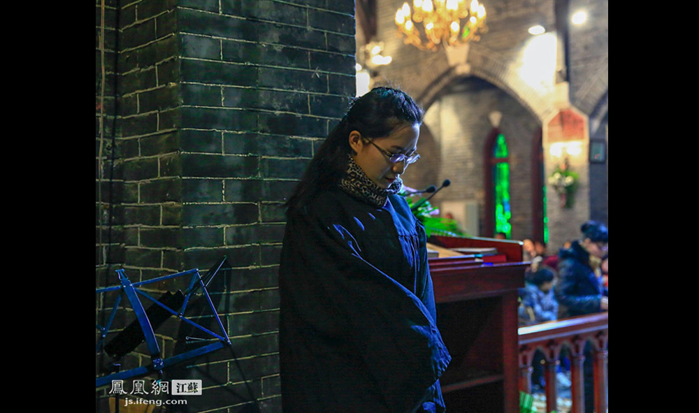 晚18时30分,圣保罗堂的平安夜崇拜活动开始。上台布道前,倪传道士在后台低头祷告。(盛明珠/摄 胥大伟/文)