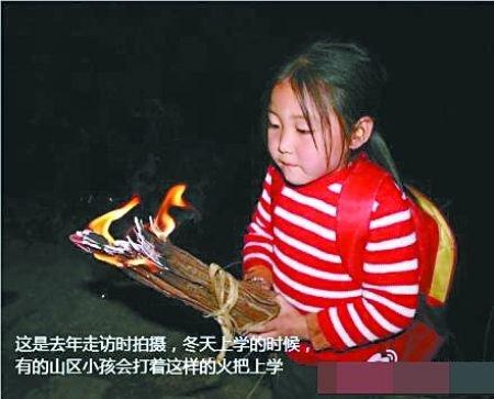 有小女孩打着火把上学
