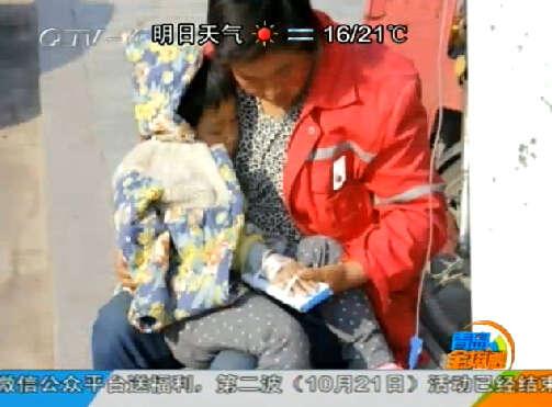 青岛一环卫工妈妈抱孩子路边打吊瓶引关注