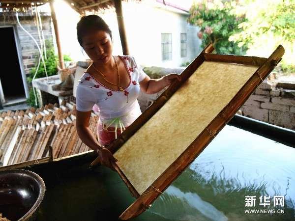 """芒团村村民取下已晒干的纸张 芒团村是位于云南省耿马县孟定镇的一个傣族聚居村落。数百年来,这里的一代代村民将一项古老的傣族手工造纸工艺传承至今。据介绍,傣族手工造纸于2006年被列入首批国家级非物质文化遗产保护名录。其手工造纸工艺仍保留着我国古代的一整套造纸工序,分为浸泡、蒸煮、淘浆、抄纸、晾晒5个流程,共11道工序,堪称中国古代造纸术的""""活化石""""。据了解,如今村里生产的纸主要作为茶厂普洱茶的包装以及为游客提供的各种纸工艺品。"""