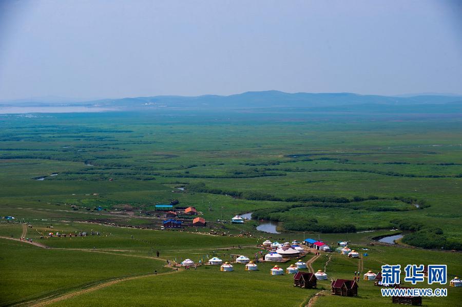 5日,游客们在乌拉盖草原上拍照.进入7月份,内蒙古草原迎来了