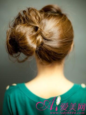 再将的头发分为二分之一,扎成蓬松的花苞头造型,用发夹固定