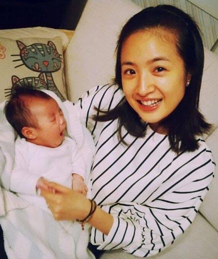照片中,林依晨素颜坐在沙发上,一手抱着star,一手则牵着小手,对镜头