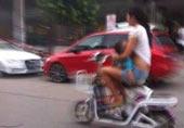 女子边骑摩托车边撩起衣服给孩子喂奶