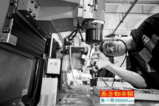巨冈机械公司,工作人员正在调试即将出厂的数控机床
