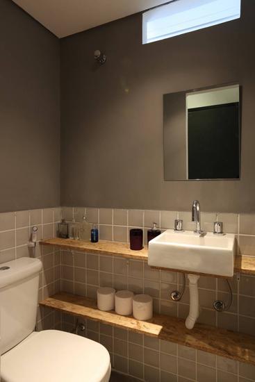 小洗手间的装饰风格也趋于简约,木质台面用于摆放物品,白色的洗手台小