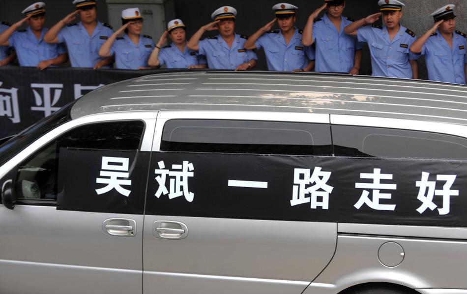 """6月4日,在交警的开道下,载有吴斌的灵车在西湖边驶过。当日下午,杭州""""最美司机""""吴斌出殡。殡仪车从吴斌居住的小区出发,沿着西湖绕行一周后驶向杭州市殡仪馆。数千名群众自发来到路口,送别英雄最后一程。新华社记者黄宗治摄"""