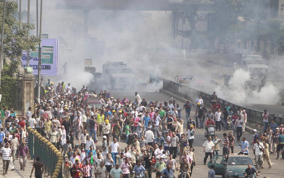 人民网8月14日讯 据CNN报道,埃及警方开始对前总统穆尔西支持者聚集的两处开罗营地进行清场,铲除帐篷,投放催泪弹,驱逐示威者。一处是开罗东部的Rabaa al-Adawiya清真寺,另一处是开罗西部的纳哈达广场。图为埃及警方驾驶车辆投放催泪弹。