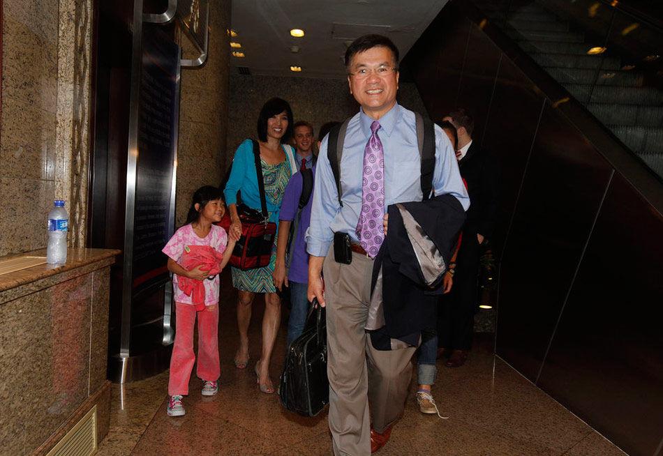 """11月20日,骆家辉发表声明,宣布辞职。他在香港《南华早报》刊登声明,称""""担任驻华大使是我一生的荣耀,我非常感谢总统奥巴马给予我到北京履职的机会。在过去的两年半时间里,我是第一个担任此职位的华裔。为美国帮助管理世界上最重要的双边关系之一是一个巨大的、有回报的挑战。代表美国在中国居住对我的家庭也是令人激动的特权""""。图为2011年8月12日,骆家辉身背双肩包携家人低调抵京。"""