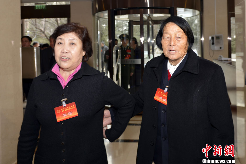 """3月2日,参加十二届全国人大一次会议的山西代表团抵达北京。唯一连任12届的全国人大代表、84岁的申纪兰携手""""铁姑娘""""郭凤莲抵达驻地报到。中新社发 韦亮 摄"""