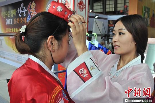 青海/图为两名青海女孩正在试穿韩服。中新社发胡友军摄