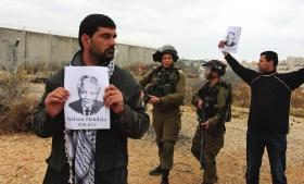 当地时间12月6日,约旦河西岸,巴勒斯坦民众拿着曼德拉画像举行示威。图/CFP
