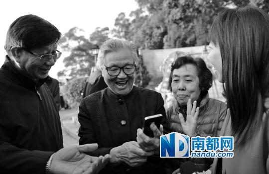 邓先群(左二)看到小平当年在中山时的资料图后一脸兴奋,旁边的女子是当年与邓小平合过影的谭志颖。 南都记者 叶志文 摄