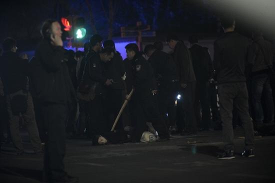 昨晚,昆明火车站广场上,警察围着一名疑似被处置的的歹徒。