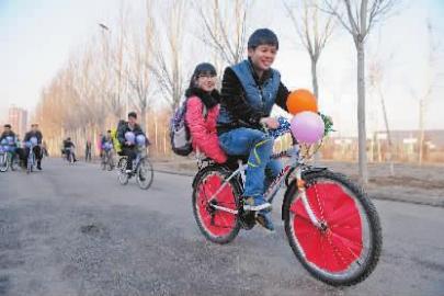 男生们骑着自行车送女生去上课 本报记者 阚旋 摄
