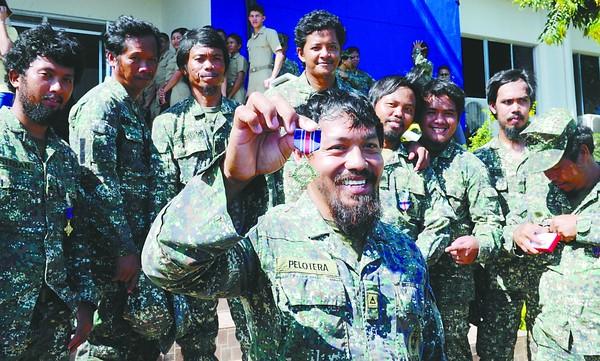 """3月31日,从仁爱礁""""换防""""下来的菲士兵炫耀获得的奖章。"""
