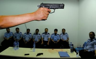 """在一堂枪械教学课上,教官向参训民警们讲解警用手枪的特点和正确握姿。(资料图片)京华时报记者董世彪摄src=""""http://y1.ifengimg.com/cmpp/2014/04/04/01/af00b4f0-d382-4be3-b6f4-43eaf4d7a34d.jpg"""""""