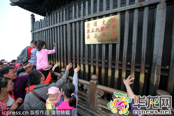 2014年4月5日,湖北武當山景區,部分游客無視景區警示牌子,隨意攀爬文物。王子瑞 / 東方IC