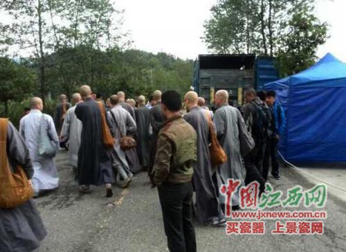 天王刘德华骑着摩托车从一队僧人旁边经过