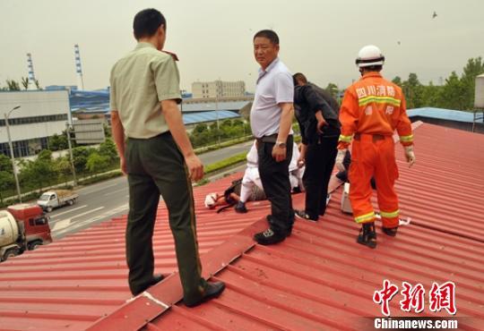 救援人员在楼顶找到受伤的男子。 谭成林 摄