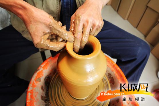 做好的成品坯子进行晾晒后才能装窑。张泰源 摄 长城网廊坊5月8日电(杨巍 记者刘振山)虽然制作陶器很多步骤都能用现代的机器代替,但王秀还保留着传统的手工制作。这名62岁的固安县手工艺人用双手传承着数千年历史的手工陶艺。 5月8日,我们走近了这位陶艺传承人,听他诉说制陶的经历。  自幼喜好书画 王秀出生于1952年,祖辈和父辈都是靠着生产陶艺花盆、面盆为生。他自幼就喜好书画,经常买来窗户纸在上面作画。也许是因为这种积累为他日后在陶器上雕刻、在脸谱模型上绘画打下了基础。初中毕业后,他就随爷爷和父亲继续坚守着