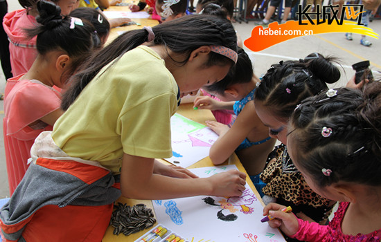 和小朋友一起画画。翟占一 摄 星城国际社区站长王娟说,六一儿童节马上就要到了,组织一些健康的孩子来这里演出,想来想去,舞蹈是最好的方式,只想给这里的孩子做点力所能及的事情。12名小拉丁舞演员,年龄最小的只有5周岁,最大的也不过12岁。他们穿着专业演出服装,认真用心地跳着恰恰、伦巴,一板一眼,有模有样。在小演员演出的间隙,邯郸市特教学校的孩子主动给他们搬去凳子,拍拍他们的肩膀,用手指指凳子,让他们坐下休息一会儿。邯郸市特教学校的孩子们脸上溢满笑容,不停鼓掌欢迎。这个学校也有一支舞蹈队,原本打算也
