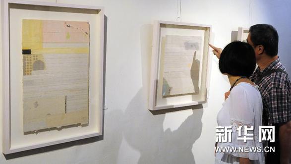 17日,观众在欣赏抽象水墨艺术家梁铨的作品《一味》(右).新华