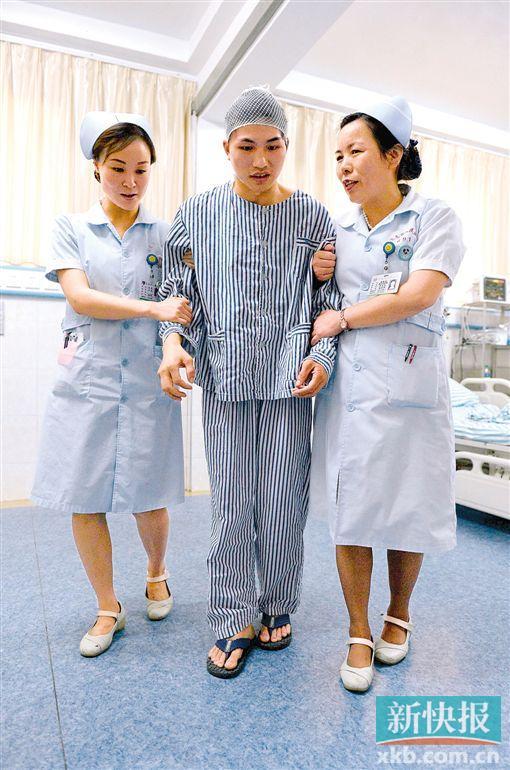 6月12日,柳艳兵由医护人员陪护下床进行简单活动.新华社发