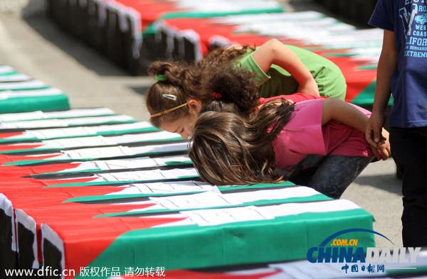 拉姆/巴勒斯坦女孩参加示威活动,亲吻用作象征的假棺材。