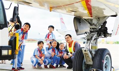 图为小学生在飞机起落架下观看飞机的细节.