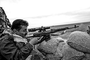 """12月12日,在伊拉克北部的摩苏尔市以东约30公里,库尔德武装士兵向被""""伊斯兰国""""武装分子控制的村庄射击。  新华社发"""