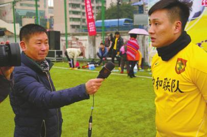 领队李鲤帮记者拿话筒采访。