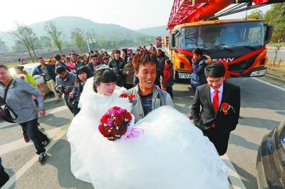 新郎把新娘从驾驶室抱出来后,新郎的4位家属接力抱新娘入新房。