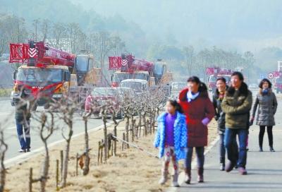 霸气的迎亲车队来到花山何董村村口,不少村民前来观望。