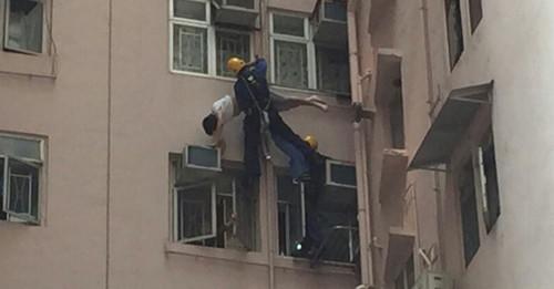 男子长裤被晾衫架勾住,吊悬在半空。(图:香港《明报》网站)